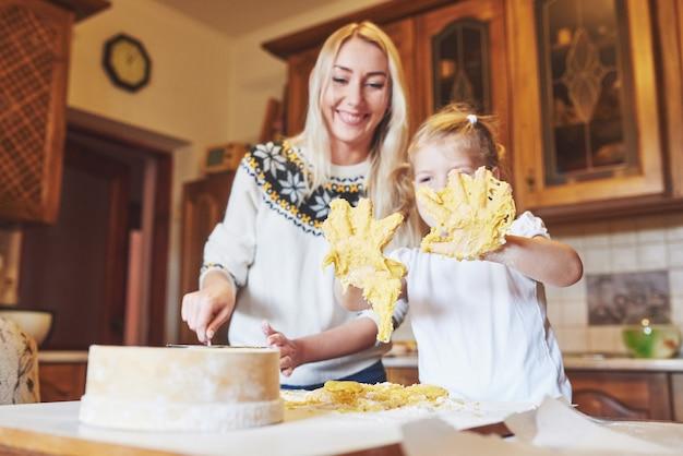 幸せな娘とママのキッチンでクッキーを焼く