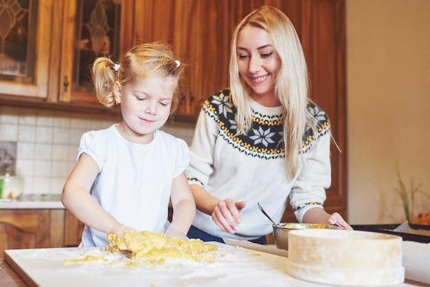 台所で幸せな笑顔のお母さんは彼女の娘と一緒にクッキーを焼きます。