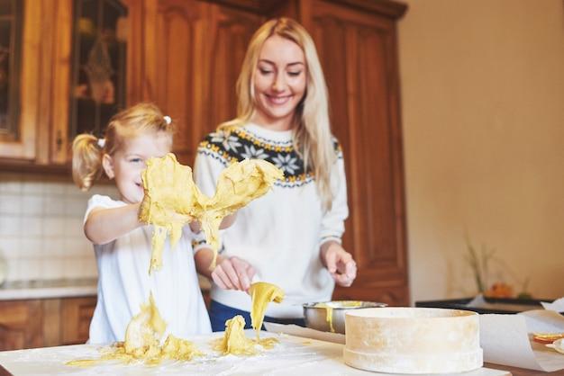 Счастливая дочь и мама на кухне пекут печенье