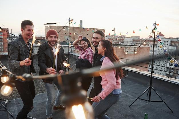 幸せな休日。屋上で花火を遊んでいます。若い美しい友人のグループ