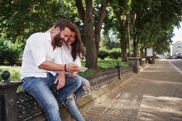 市内の晴れた日にスマートフォンを見て若いカップル