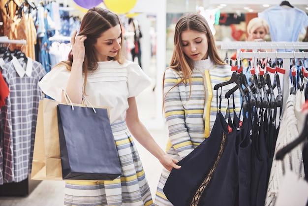 Молодые красивые женщины на еженедельном рынке ткани. лучшие друзья получили свободное время, веселились и делали покупки