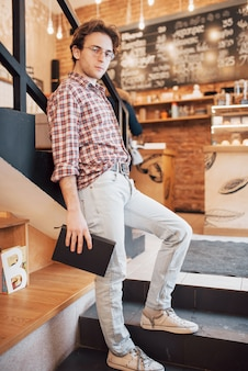 コーヒーショップでノートを保持しているカジュアルなシャツの才能のある若い男。