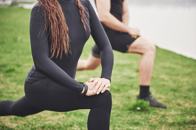 水の近くの公園で屋外ストレッチフィットネスカップル。若いあごひげを生やした男性と女性が朝一緒に運動