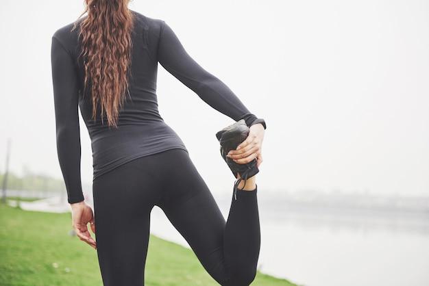 Молодая бегунья фитнеса разминает ноги перед бегом по парку