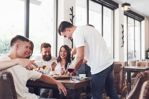 Вкусная пицца на столе, с группой молодых улыбающихся людей, отдыхающих в пабе