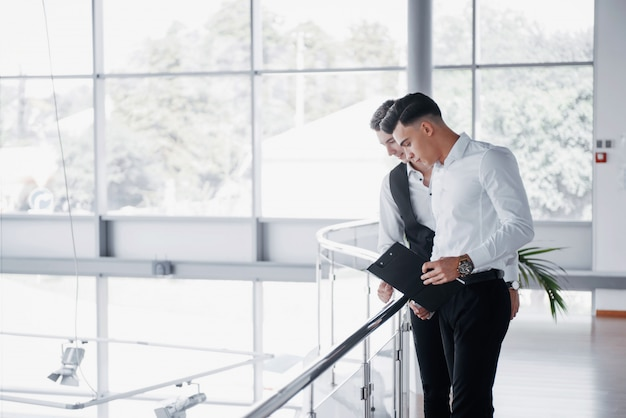 オフィスの手すりに立っているドキュメントや製品を見て若いビジネスマン