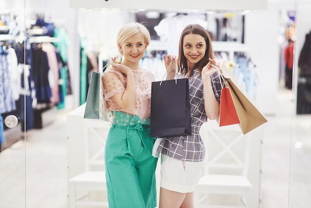 Отличный день для покупок. две красивые женщины с сумками смотрят друг на друга с улыбкой во время прогулки по магазину одежды