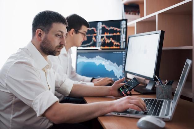 株式仲買人のチームが、ディスプレイ画面のある暗いオフィスで会話しています。投資を目的としたデータ、グラフ、レポートの分析。クリエイティブチームワークトレーダー