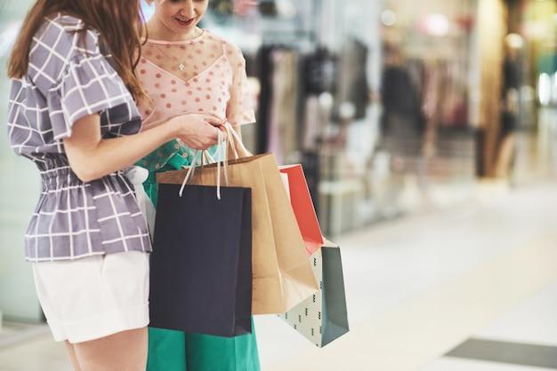 Отличный день для покупок. две красивые женщины смотрят на сумку и хвастаются тем, что купили
