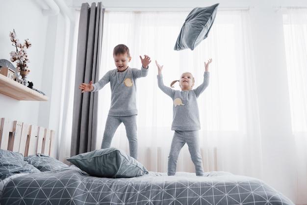 白い寝室で遊んで幸せな子供たち。男の子と女の子、兄と妹はパジャマを着てベッドで遊んでいます。赤ちゃんと幼児のためのナイトウェアと寝具。自宅での家族