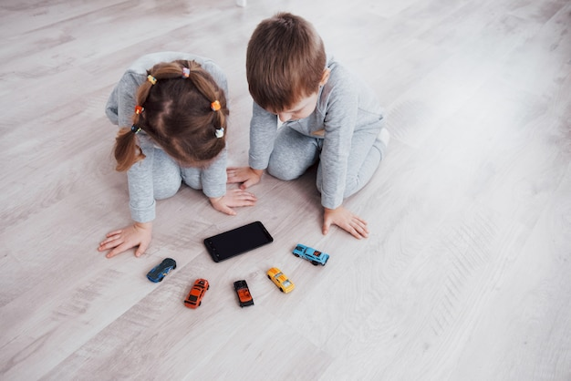 上面図。家庭でデジタルガジェットを使用する子供たち。パジャマを着た兄と妹が漫画を見てテクノロジータブレットでゲームをプレイ
