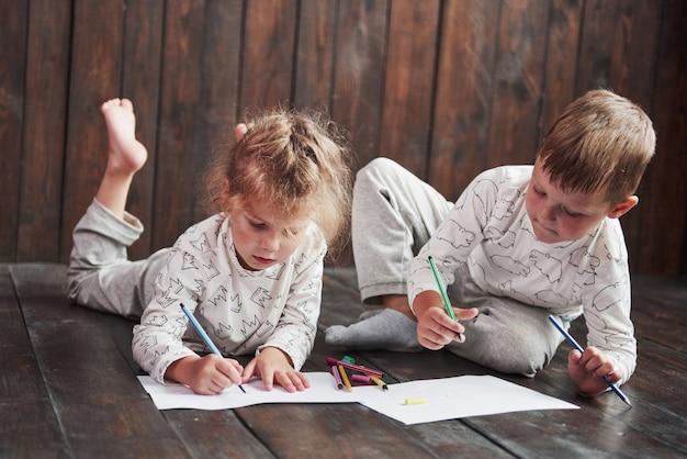 子供たちはパジャマを着て床に横になり、鉛筆で絵を描きます。鉛筆で描くかわいい子