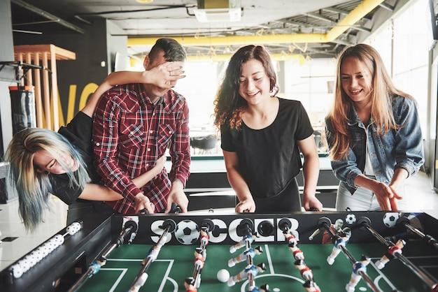 Улыбающиеся молодые люди играют в настольный футбол в помещении
