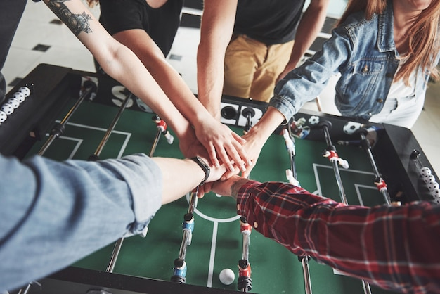Друзья вместе играют в настольные игры, настольный футбол, весело проводят время.