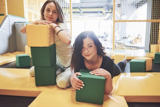Компания - молодая женщина, которая развлекается с мягкими блоками на детской площадке в батутном центре.