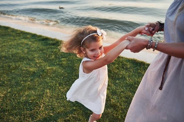 ママと彼女の小さな娘は湖の近くの芝生で遊んでいます。