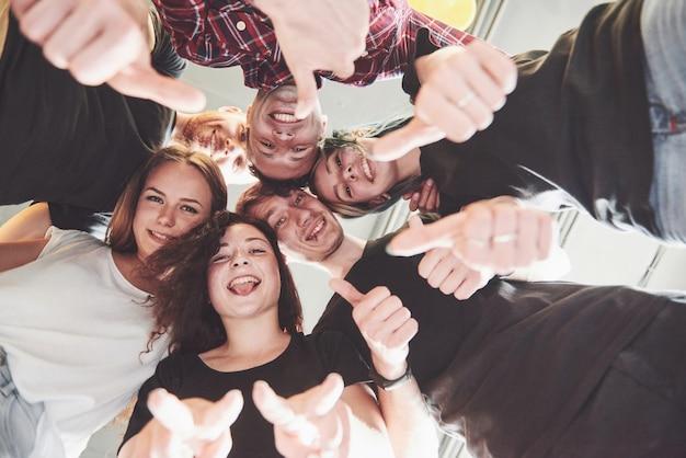 Счастливая группа друзей с их руки вместе в середине