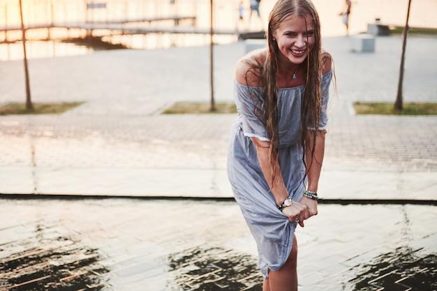 Девушка в брызгах воды в фонтане.