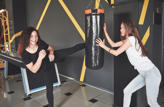 Портрет веселых боксеров, одетых в джинсы и футболки в игровом центре.