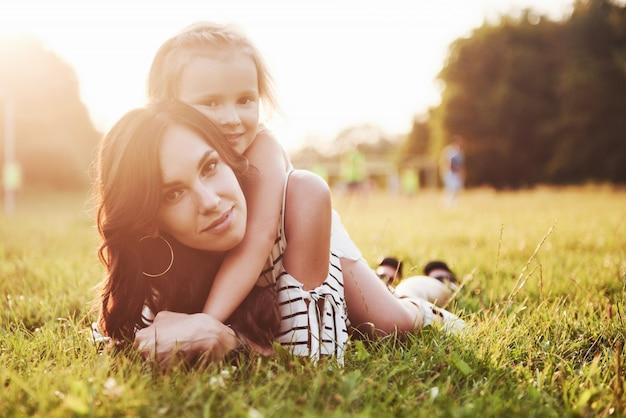 ハーブの明るい夏の太陽の下で公園でハグする母と娘。