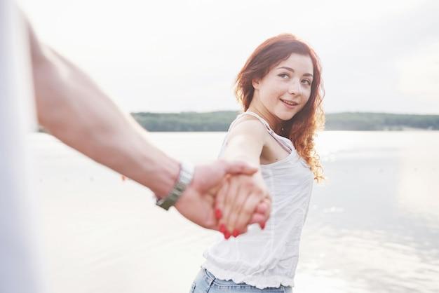 遊び心のある表情と夫との手で笑顔の幸せな女性。