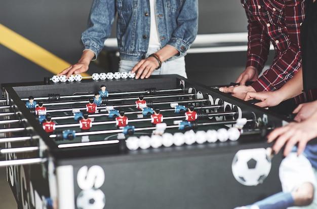 Улыбающиеся молодые люди играют в настольный футбол на отдыхе