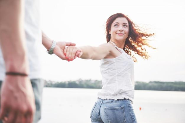 ビーチで面白い遊び心のある幸せなカップルを愛する。