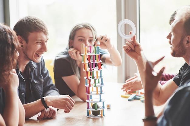 木製のテーブルに座っている創造的な友人のグループ。