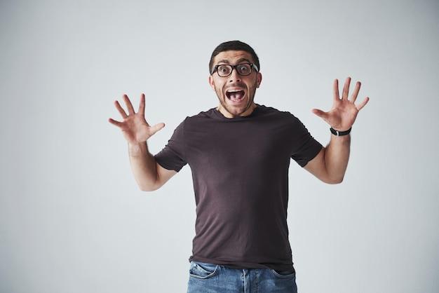 カジュアルな服装の感情的な男は、痛みや恐怖で悲鳴を上げます。