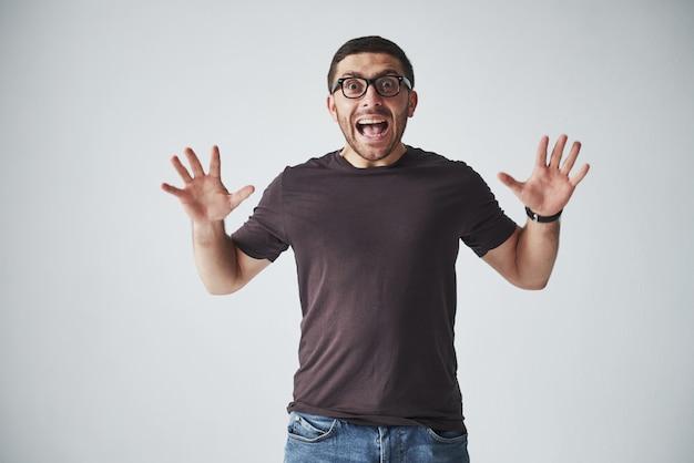 カジュアルな服装の感情的な男は、痛みや恐怖で悲鳴を上げます。彼の気持ちは圧倒的です