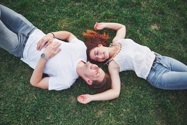 公園の芝生の上で横になっている若者のロマンチックなカップル。
