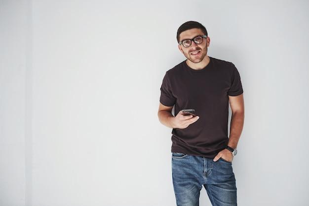 Молодой счастливый человек, одетый с смартфон на белом