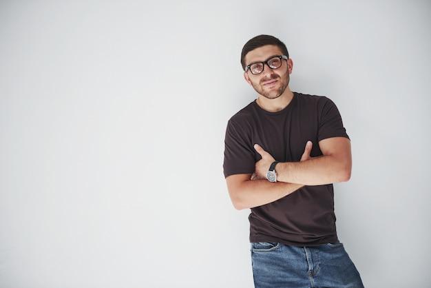 メガネをかけて喜んで笑って白で隔離される流行に敏感な若い男