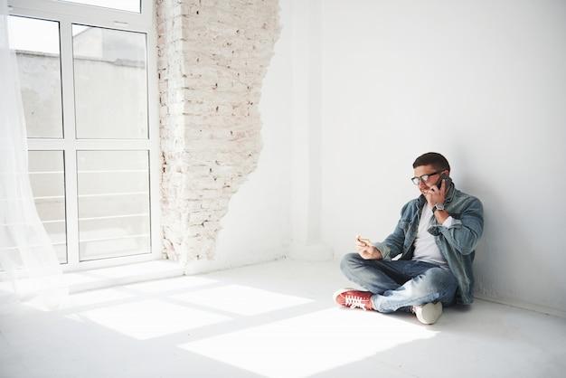 カジュアルな服装の男がクレジットカードを持っている空のアパートに家に座っています。