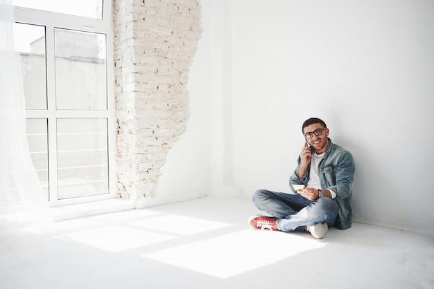 カジュアルな服を着た男が、クレジットカードを持って空のアパートに家に座って電話をかけています。