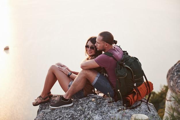 川や湖の海岸を眺めながら岩山の上に座っているバックパックとカップルを抱き締めます。
