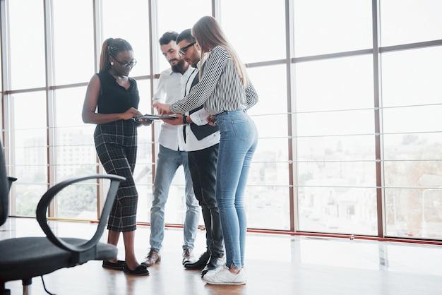 若いビジネスマンがオフィスでの会議中に新しい創造的なアイデアを一緒に議論しています。