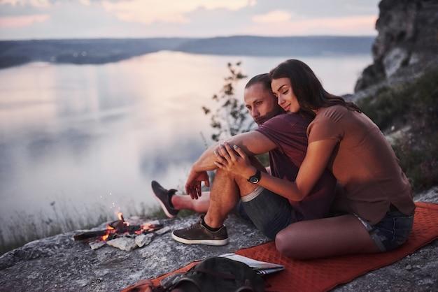Обниматься пара с рюкзаком, сидя у костра на вершине горы, наслаждаясь видом на побережье реки или озера.