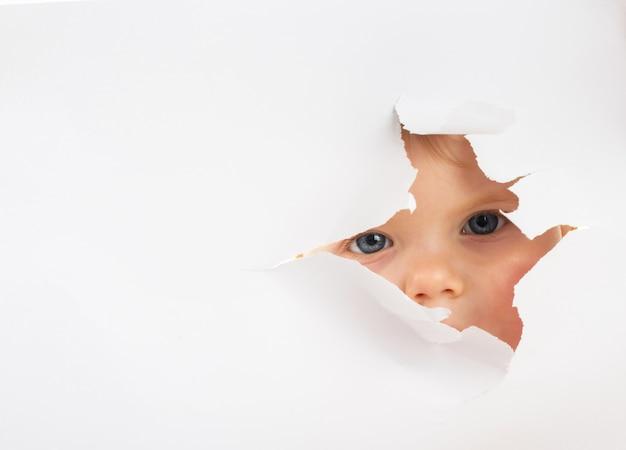穴から外を見て小さな赤ちゃん