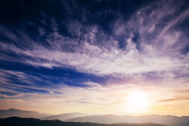 山の太陽を背景にカラフルな空。