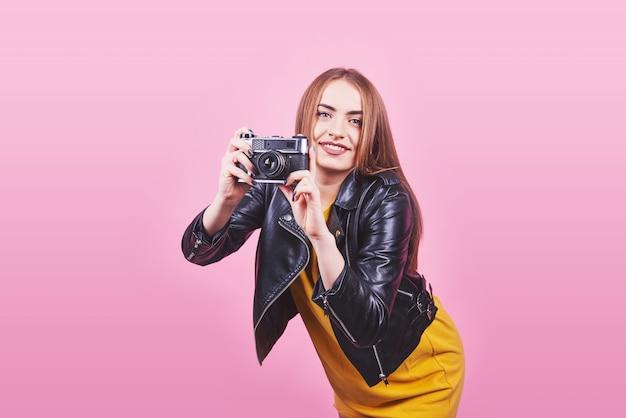 Модная внешность, довольно крутая модель молодой женщины с ретро пленочной камерой в черной куртке на розовом