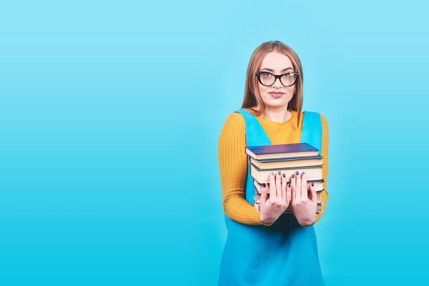 カラフルな青に分離された本の山を手で保持している混乱のかわいい女の子