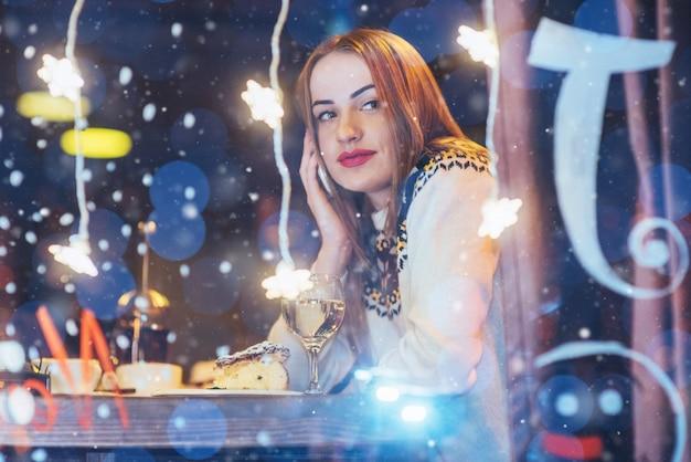 カフェに座って、ワインを飲む若い美しい女性。クリスマス、新年、バレンタインデー、冬休み