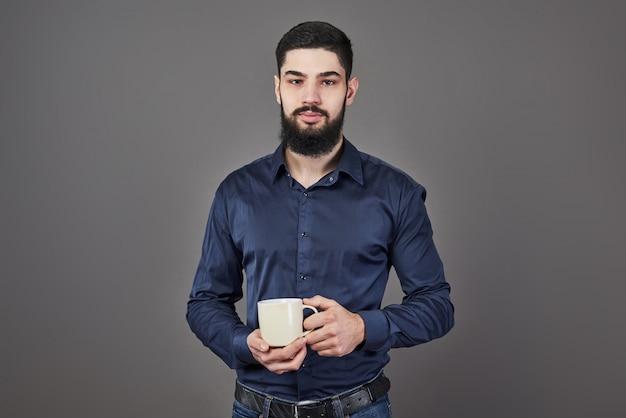 Красивый бородатый мужчина со стильной бородой и усами на серьезном лице в рубашке, держащей белую чашку или кружку, пьющей чай или кофе в студии на сером