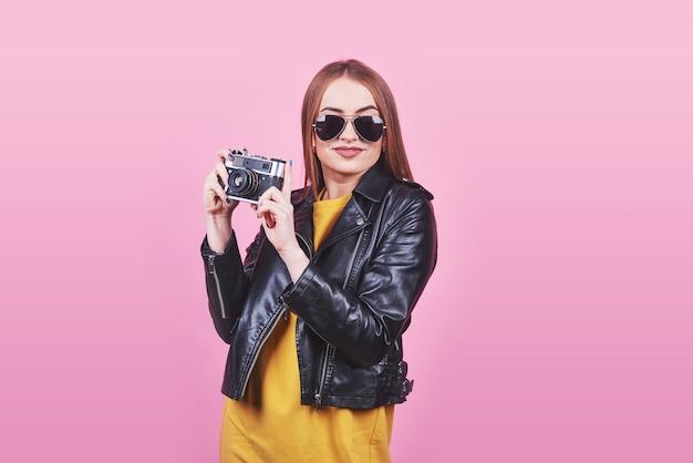 Модный взгляд, довольно крутая модель молодой женщины с ретро фильмом в черной куртке, против розового с копией пространства