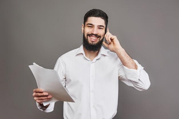 Деловой человек с бородой в белой рубашке с документами и телефоном на сером