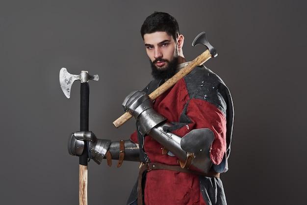 Средневековый рыцарь на сером. портрет жестокого грязного лица воина с кольчужными доспехами красно-черной одежды и боевого топора