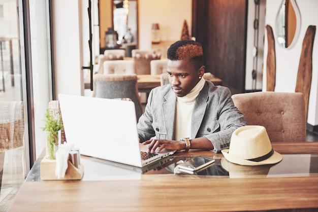 Афро-американский мужчина сидит в кафе и работает на ноутбуке