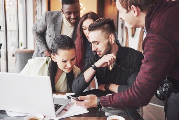 Женщина показывая коллегам что-то на портативном компьютере по мере того как они собирают вокруг стола переговоров